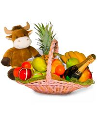 A basket of delicious fruit along with a cute stuffed animal and a bottle of sparkling wine.